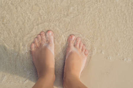 Legs of a woman on a white sand beach Stock Photo