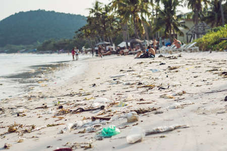 Garbage on a beautiful beach with white sand. Contamination of the environment concept.