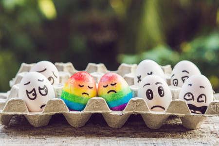 差別ゲイの概念。同性愛カップルの形で2つの虹の卵。そして、周りの人々を非難します。 写真素材