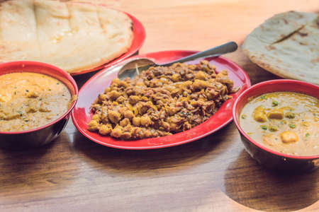 Indian Food or Indian Curry in a copper brass serving bowl with nan bread or roti.