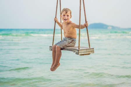 Happy boy sit on swing at the sea shore on sunset. 版權商用圖片