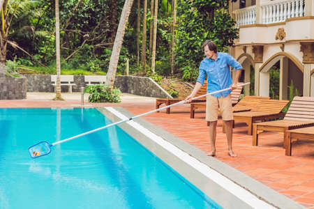 Cleaner of the swimming pool . Man in a blue shirt with cleaning equipment for swimming pools, sunny. Stok Fotoğraf