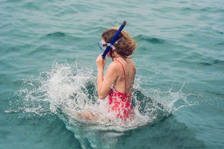 A woman jumps into the water to do snorkeling.