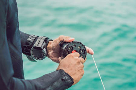 Diver prepares his equipment for diving in the sea. Stock Photo