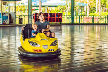 Father and son having a ride in the bumper car at the amusement park. Banque d'images