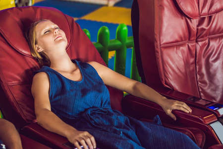 Beautiful young lady relaxing in the massage chair. Фото со стока