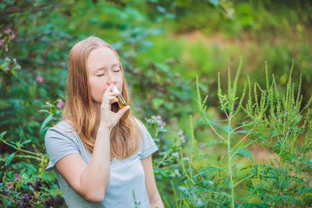 Young woman uses a spray from an allergy because of an allergy to ragweed. Stock Photo