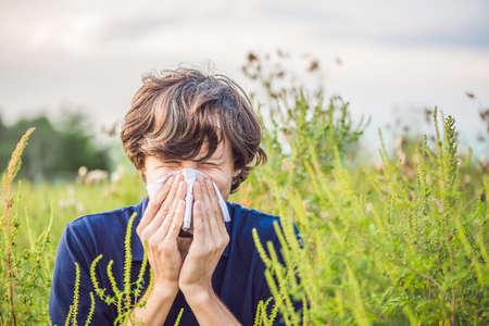 Młody człowiek kicha z powodu uczulenia na ambrozję.