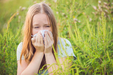 Young woman sneezes because of an allergy to ragweed. Stock fotó