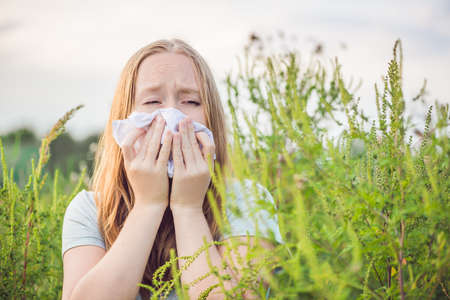 Young woman sneezes because of an allergy to ragweed. Фото со стока