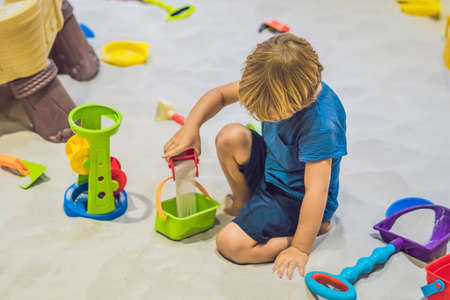 Boy playing with sand in preschool. The development of fine motor concept. Creativity Game concept. Stock Photo