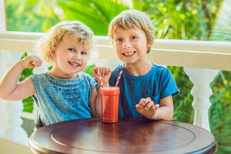 Children boy and girl drink orange smoothie from papaya. Stock Photo