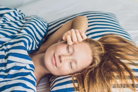Young beautiful woman sleeping in her bed and relaxing in the morning. Stock Photo