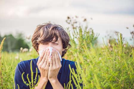 Un jeune homme éternue à cause d'une allergie à l'herbe à poux. Banque d'images