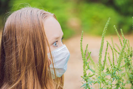 Young woman in a medical mask because of an allergy to ragweed.