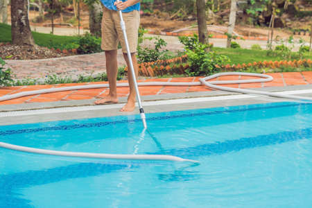 Cleaner of the swimming pool . Man in a blue shirt with cleaning equipment for swimming pools, sunny. Standard-Bild