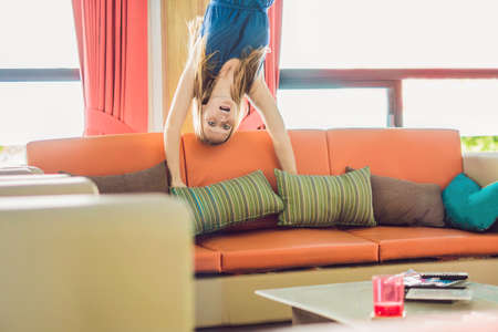 A woman is standing on his hands upside down in the living room.