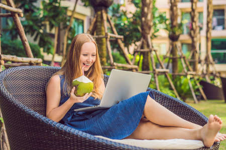 Young female freelancer sitting near the pool with her laptop in the hotel browsing in her smartphone. Busy at holidays. Distant work concept. Copy space for your text.