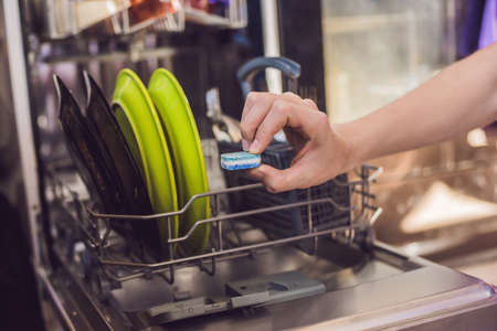 Dishwasher with dirty dishes. Powder, dishwashing tablet and rinse aid. Washing dishes in the kitchen. Stock Photo