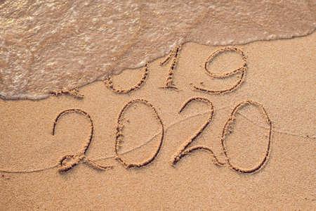 新年2020はコンセプトが来ています - 碑文2019と2020ビーチ砂、波はほぼ数字2019をカバーしています。 写真素材