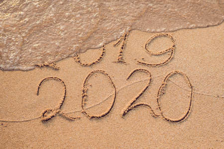 New Year 2020 is coming concept - inscription 2019 and 2020 a beach sand, the wave is almost covering the digits 2019.