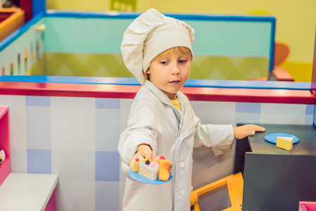 The boy plays the game as if he were a cook or a baker in a children's kitchen.