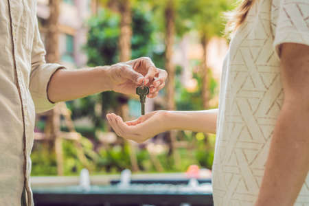 Real estate agent giving keys to apartment owner, buying selling property business. Close up of male hand taking house key from realtor. Mortgage for purchasing flat, getting access to own home.