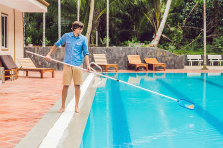 Cleaner of the swimming pool . Man in a blue shirt with cleaning equipment for swimming pools, sunny. 스톡 콘텐츠