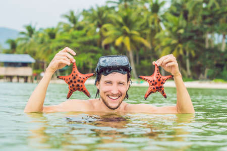 Happy young scuba diver holding sea star, smiling, looking at camera.