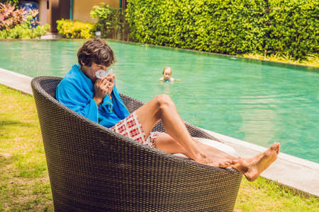 Sick man traveler. The man caught a cold on vacation, sits sad at the pool drinking tea and blows his nose into a napkin. Stock Photo