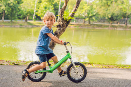 Little boy on a bicycle. Caught in motion, on a driveway. Preschool childs first day on the bike.