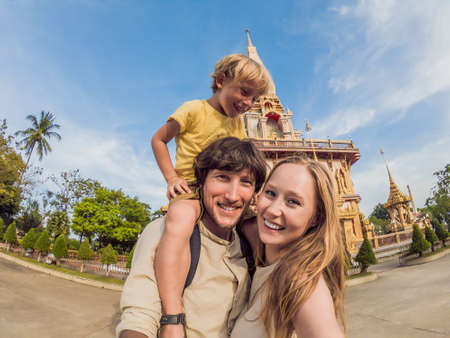 A happy family of tourists on the background of Wat Chalong in Thailand. Traveling with children concept.
