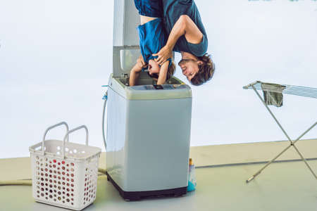 Father tries to wash his son in a washing machine standing upside down with his feet.