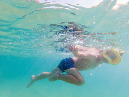Child wearing snorkeling mask diving underwater in the sea
