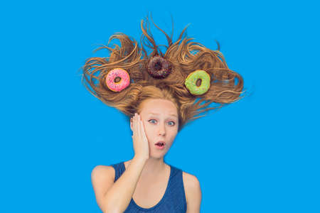 Young woman with donuts in her hair. Multicolored donuts. Harm of sweet. Stock Photo