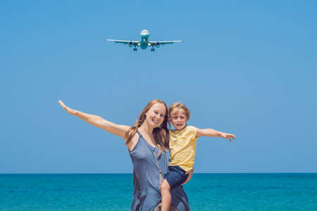 Mother and son have fun on the beach watching the landing planes. Traveling on an airplane with children concept. Stock Photo