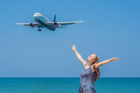 Young woman on the beach and landing planes. Travel concept.