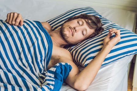 Man sleeping on his bed in bedroom at home.