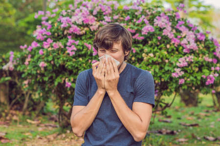 Young man sneezes because of an allergy to pollen.