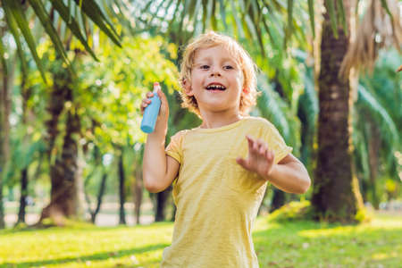 Boy spraying insect repellents on skin in the park.
