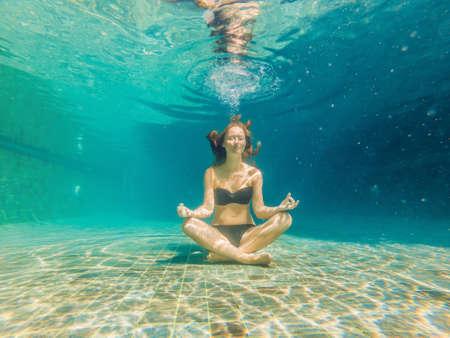young woman in black bikini in yoga position underwater in diving aquarium, full body shot, front view.
