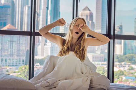 Woman wakes up in the morning in an apartment in the downtown area with a view of the skyscrapers. Life in the noise of the big city concept. Not enough sleep.