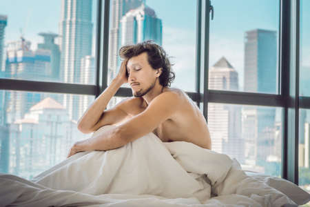 Man wakes up in the morning in an apartment in the downtown area with a view of the skyscrapers. Life in the noise of the big city concept. Not enough sleep.