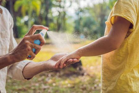 Vater und Sohn verwenden Mückenspray. Sprühendes Insektenschutzmittel auf der Haut im Freien.