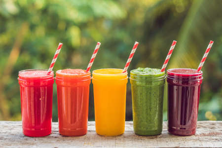 Rainbow from smoothies. Watermelon, papaya, mango, spinach and dragon fruit. Smoothies, juices, beverages, drinks variety with fresh fruits on a wooden table.