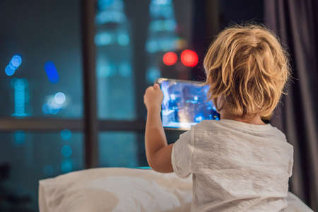 The boy uses the tablet in his bed before going to sleep on a background of a night city. Children and technology concepts Foto de archivo