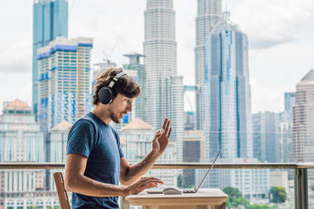Young man teaches a foreign language or learns a foreign language on the Internet on her balcony against the backdrop of a big city. Online language school lifestyle Stok Fotoğraf