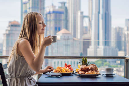 A young woman is having breakfast on the balcony. Breakfast table with coffee fruit and bread croisant on a balcony against the backdrop of the big city