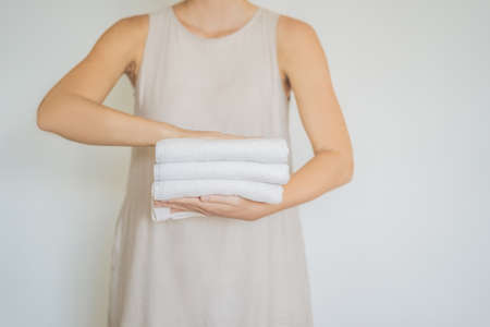 A woman is holding a stack of white towels. Concept of service in hotels, laundry, spa. Stock Photo