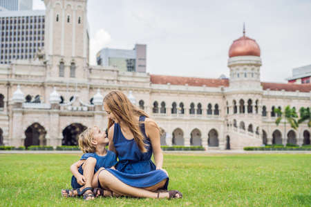 Mom and son on background of Merdeka square and Sultan Abdul Samad Building. Stock Photo